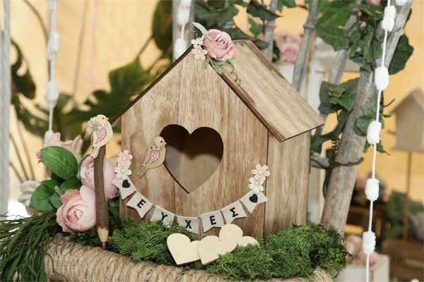 Ξύλινο κουτί σε σχήμα σπιτάκι για πουλάκια, με ξύλινες καρδιές για να γράφουν οι καλεσμένοι τις ευχες. Με στυλό από κλαδί δέντρου.