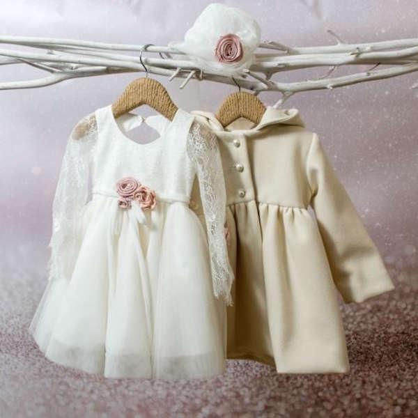 Ένα υπέροχο βαπτιστικό ρούχα σε διακριτικά χρώματα, με δαντελένια μανίκια και ανοιχτή πλάτη διακοσμημένη με λουλουδάκια, φτιαγμένο με φίνα ευρωπαϊκά υφάσματα, που θα απογειώσει την ιδιαίτερη μέρα της μικρής σας πριγκήπισσας.